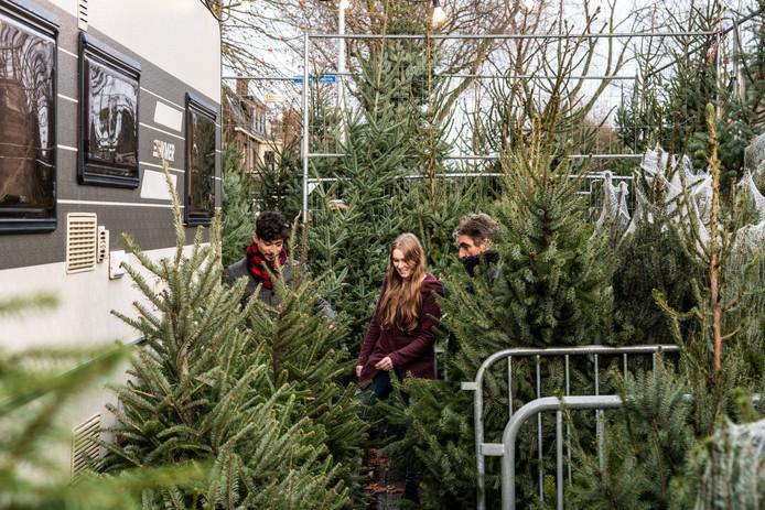 Kerstboomverkoper Ernst van der Wielen (rechts) helpt klanten op het Vierdaagseplein, waar hij de komende weken ook slaapt in een camper om een oogje in het zeil te houden.