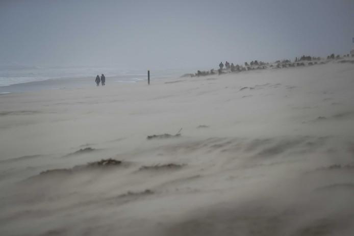 Wandelaars trotseren storm Dennis op het strand van Egmond aan Zee. Een week na storm Ciara raast er opnieuw een storm over het land heen.