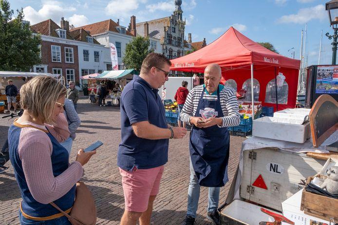 Ko Wagenaar maakt een oester open voor een klant op de Vis- en versmarkt in Veere.