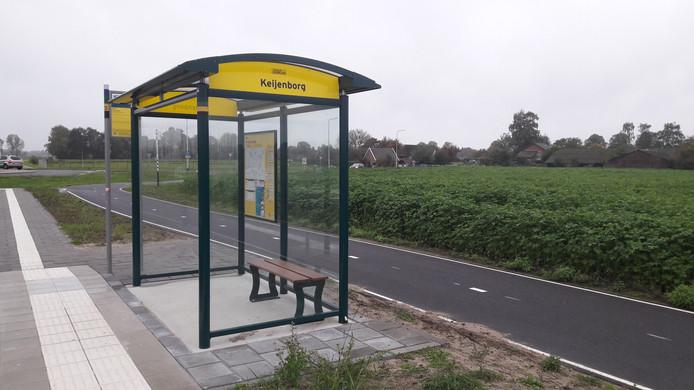 De bushalte langs de Rondweg in Keijenborg, met in de verte achter de akker de Kroezerijweg.