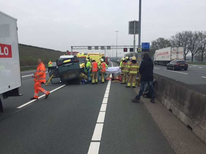 Hulpdiensten in actie bij de over de kop geslagen auto op de A12.