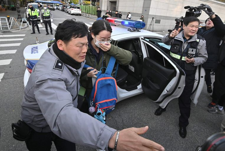 Sommige studenten komen onder politiebegeleiding aan bij het examencentrum.