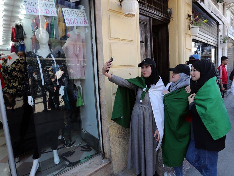 Algerijnse protestanten maken een selfie bij de protesten tegen de Algerijnse president Bouteflika.  Beeld EPA