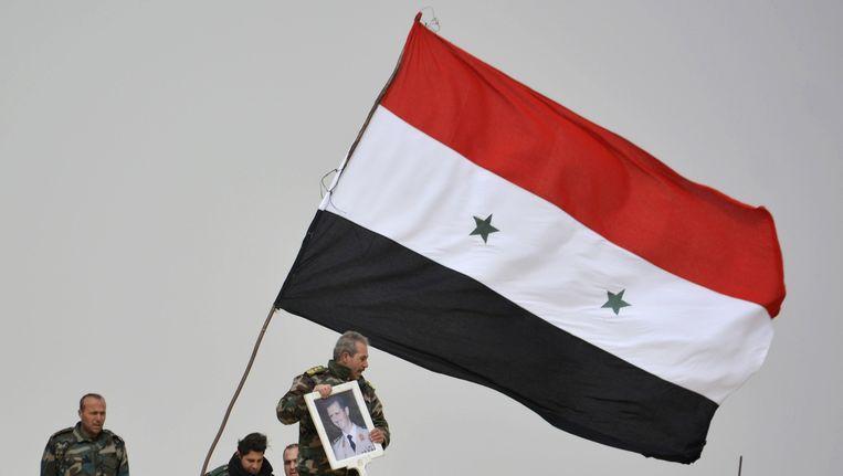 Strijders loyaal aan president Bashar al-Assad tonen zijn portret in de zuidelijke Syrische stad Deir-al-Adas.