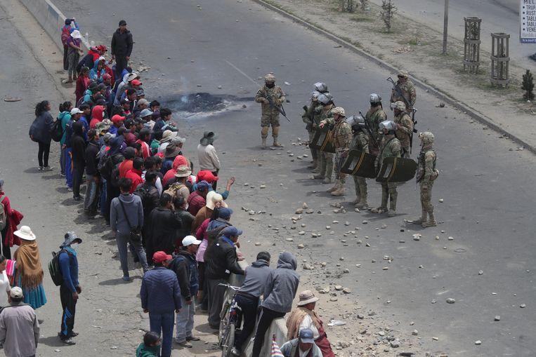 Een groepje demonstranten staat tegenover gewapende ordediensten in El Alto, Bolivia.