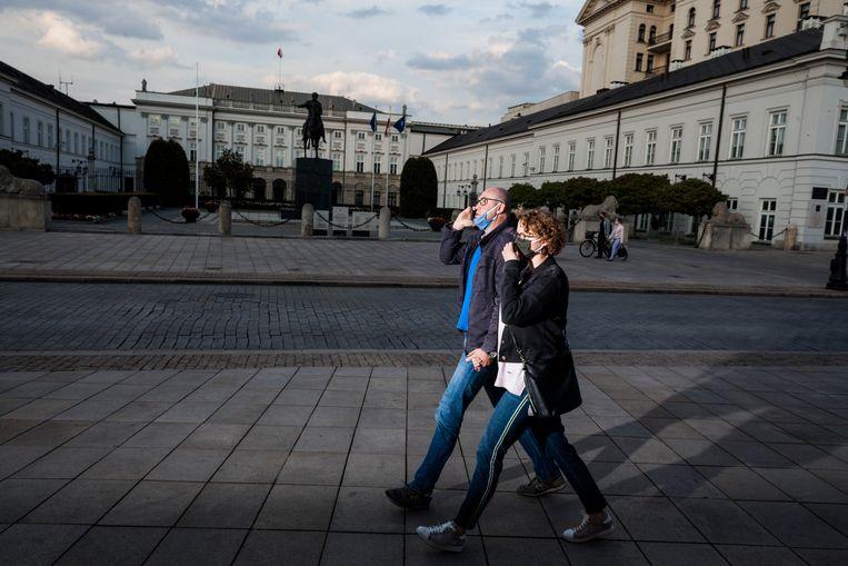 Voorbijgangers lopen met verplicht gezichtsmasker langs het presidentieel paleis in Warschau. Voor zondag 10 mei stonden er presidentsverkiezingen gepland, maar het is de vraag of en hoe die doorgang zullen vinden.  Beeld Piotr Malecki