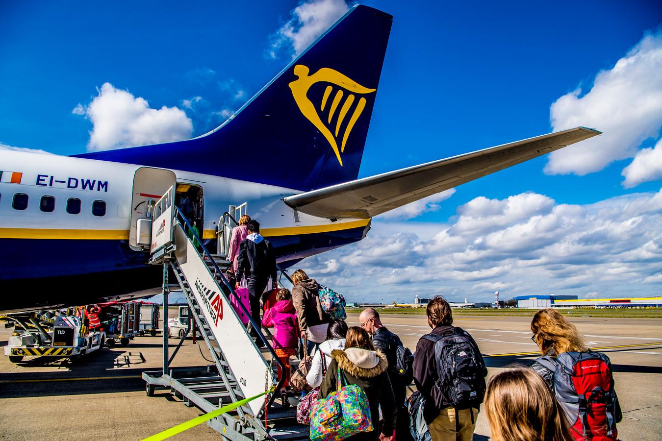 Vakantiegangers stappen het vliegtuig in.