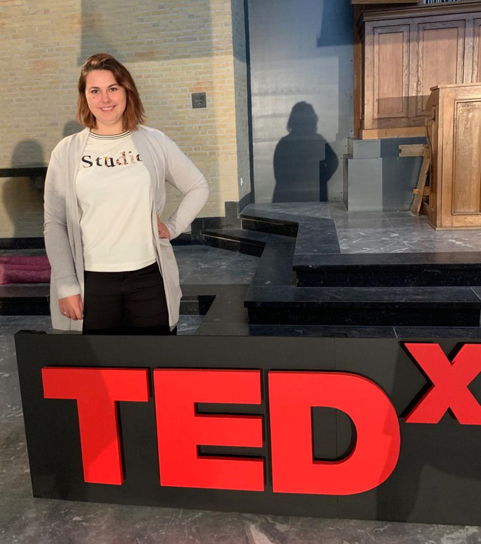 Esmee Buijze bij het logo van TEDx.