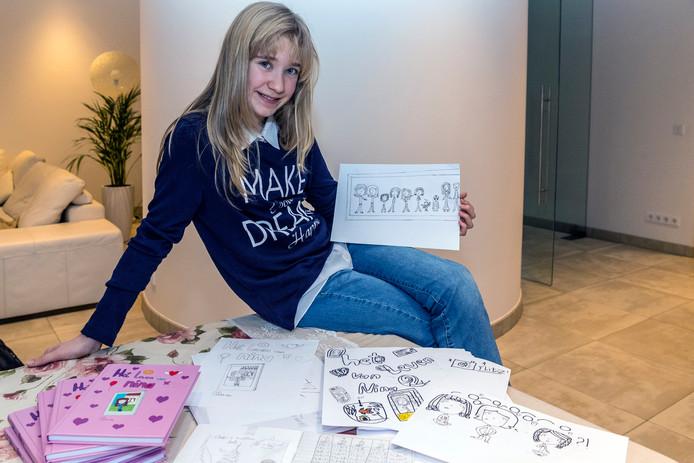 Chiara Opstal uit Hoogerheide is pas tien jaar oud, maar heeft al zelf een boekje geschreven en uitgegeven. Dat heet 'Het Leven van Nina'. Foto: Chiara met haar boek, aantekenschriften en illustraties.
