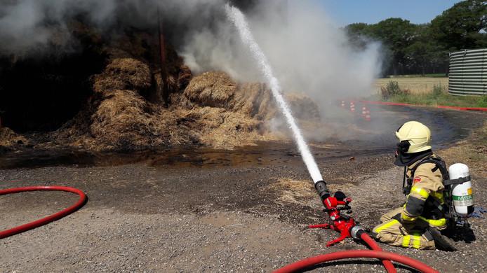 De brandweer bestrijdt de hooibrand in de kapschuur aan de Keppelbroeksdijk in Terborg.