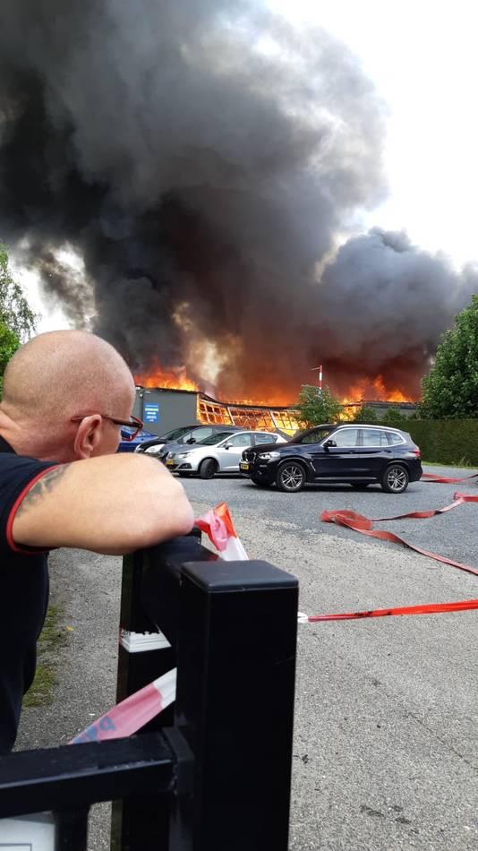 De eigenaar kijkt toe bij de brand.