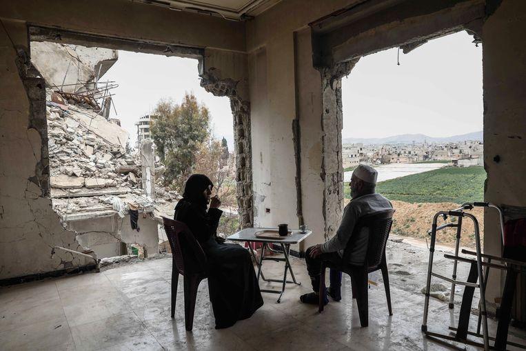 Een Syrisch stel drinkt koffie in hun verwoeste huis in Douma. Beeld AFP