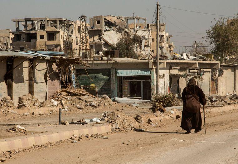 Een bewoonster loopt voorbij een verwoest gebouw in de verlaten stad Raqqa.