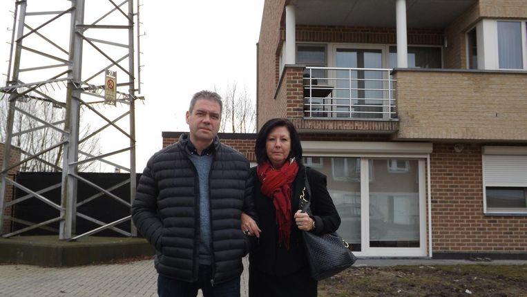 Dirk en Arlette uit Reet bij hun appartement. Ze wonen pal naast een hoogspanningsmast (zie foto boven).
