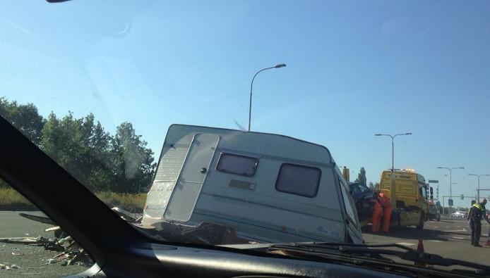 De caravan is flink beschadigd, verderop wordt de auto die op de caravan inreed op een bergingswagen getild.