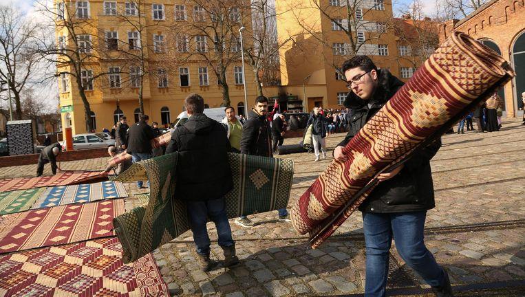 Bezoekers van de Koca Sinan Camii in Berlijn leggen hun bidkleed buiten neer, nadat hun moskee door brandbommen deels is verwoest. Beeld null