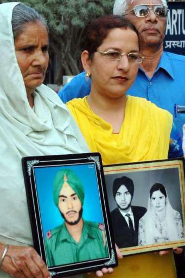 De vrouw van Singh (L) wacht haar man op met foto's van voor zijn arrestatie