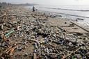 Een Indonesische man loopt over het Matahari Terbit strand in de buurt van Sanur, op Bali. Het strand is door een flinke wind veranderd in een vuilnisbelt door de aangespoelde rotzooi die bewoners en toeristen in de natuur dumpen. Foto Johannes P. Christo