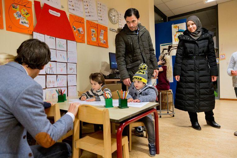 Aiman en Amneh leveren zoon Abadi af bij de peuterspeelzaal, zelf gaan ze door naar Nederlandse les. Beeld Inge van Mill