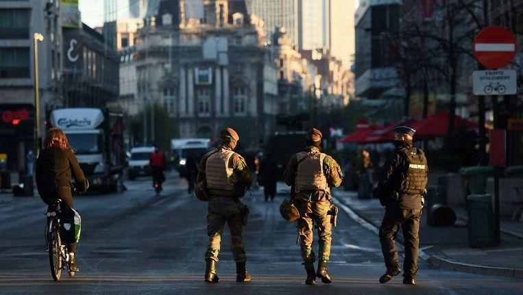 Belgische militairen en een agent in Brussel. In Brussel geldt de hoogste terreurdreiging na de aanslagen in Parijs. Beeld afp
