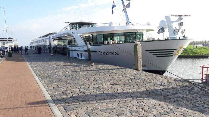Riviercruiseschip Inspire voor anker bij het havenhoofd in Willemstad.