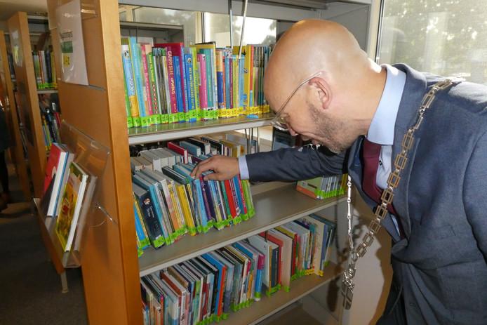 Han Looijen snuffelt tussen de nieuwe kinderboeken in nieuwe bibliotheek van De Bolster.