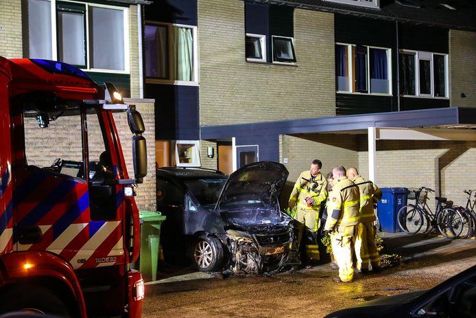 De brandweer bekijkt de schade aan de auto.