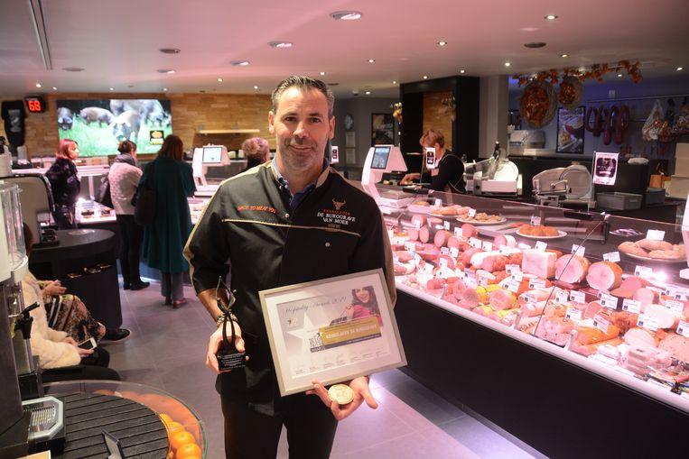 Filip De Burggrave toont trots zijn award van 'klantvriendelijkste slager'