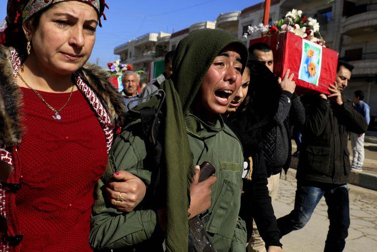 Rouwende Syrische Koerden in Afrin bij de begrafenis van gesneuvelde YPG-strijders. Beeld AFP