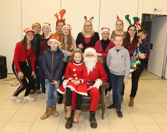 De kerstman omringd door enkele kinderen en de bestuursleden van de jeugdraad.