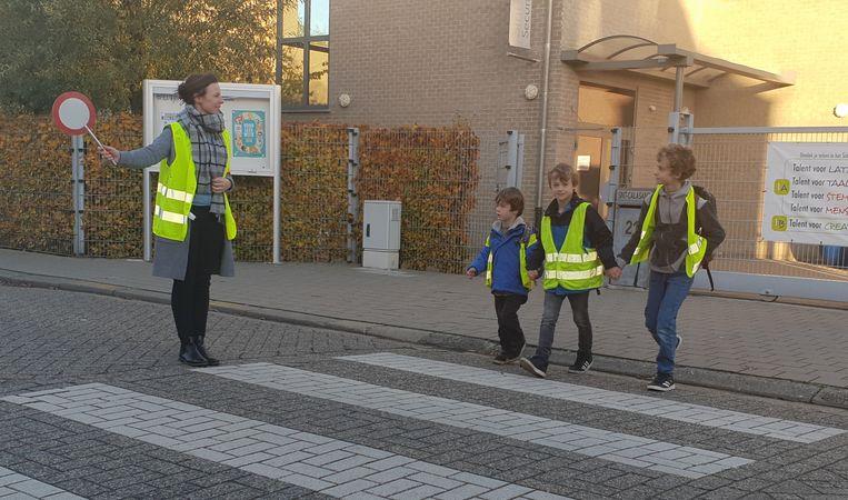 Josse (4), Door (8) en Dan (10), de kinderen van Tine. Na schooltijd begeleiden de leerkrachten de leerlingen bij het oversteken.