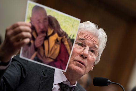 Richard Gere houdt een foto omhoog van een monnik die zelfmoord heeft gepleegd.