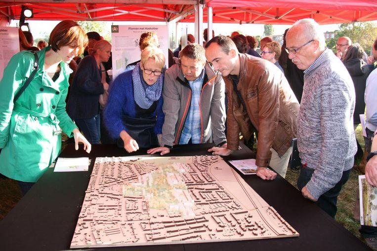 Buurtbewoners bekijken een maquette van de plannen. Na inspraak van de buurt, en met steun van Ekerse politieke partijen, komt er een aanpassing van de bebouwingsplannen.