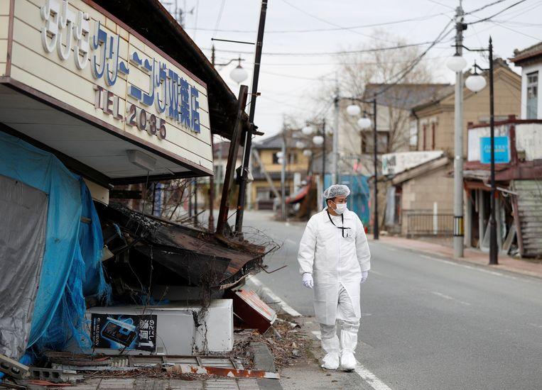 Een man in het leeggelopen gebied rond de kerncentrale. Beeld REUTERS