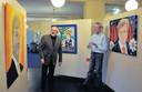 Chris Moorman (rechts) en Gerard Baan bespreken de zeven inzendingen. Baan herkent niet de koning, maar minister Opstelten in het portret met oranje achtergrond.