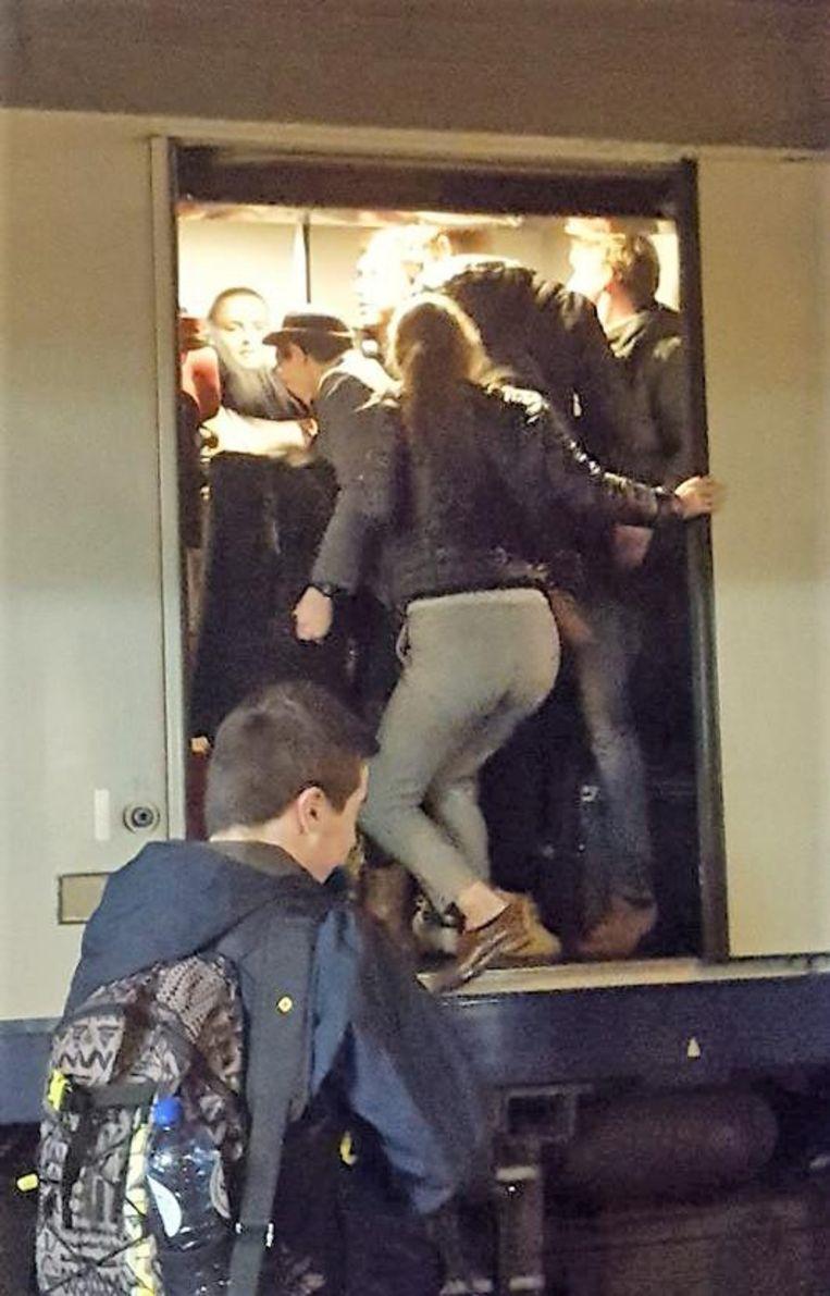 De studenten zitten als sardienen in een blik op de overvolle trein.
