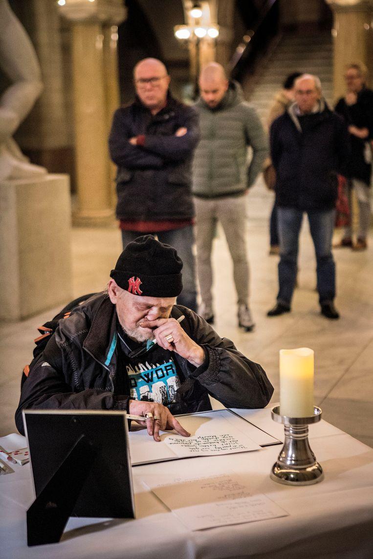 Belangstellenden tekenen het condoleanceregister voor Jules Deelder in het stadhuis.  Beeld Arie Kievit
