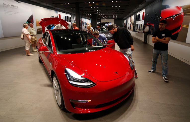 Potentiële kopers bewonderen een Tesla Model 3 in een showroom in Denver. Uit Amerikaans onderzoek blijkt dat de veiligheidssystemen van deze auto regelmatig falen.