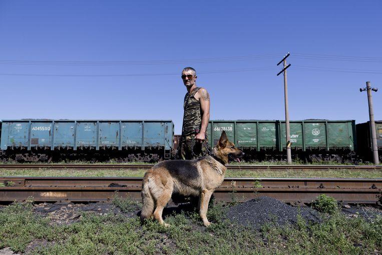 Een pro-Russische rebel bewaakt het station van Torez waar een trein met vier koelwagons met lichamen van slachtoffers van de vliegramp in Oekraine klaar staat om te vertrekken. Beeld anp