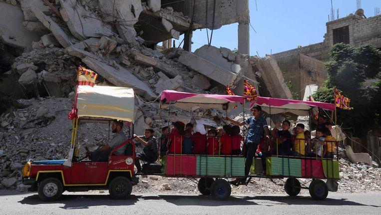 Syrische kinderen vieren het einde van de ramadan in een door rebellen bezet dorp bij Damascus Beeld AFP