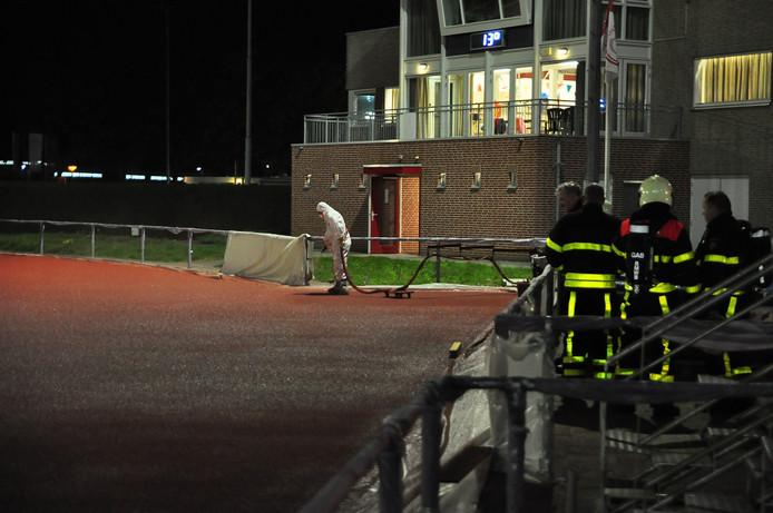 Mannen in witte pakken brengen de nieuwe laag aan op de atletiekbaan terwijl brandweerlieden toekijken.