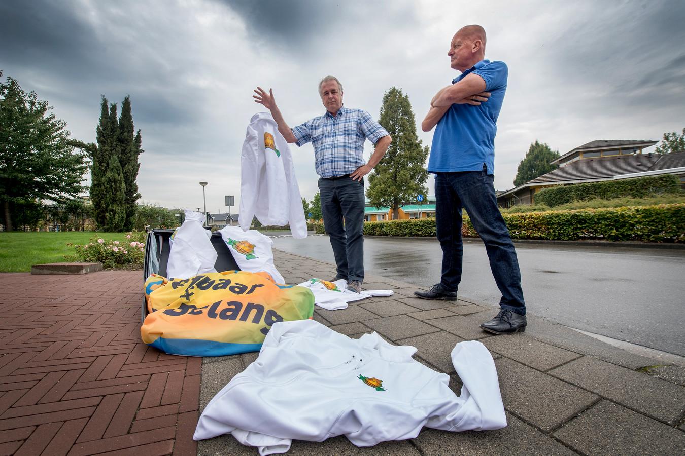 Jos Rietbergen (l) en Cees Schook dumpen symbolisch de jassen en de vlag van de partij die het levenslicht niet zal zien.