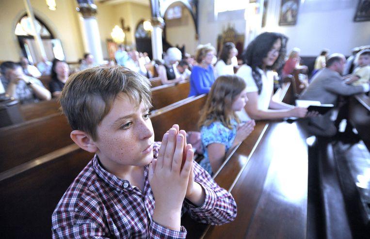 De jongen Thomas Carey bidt tijdens een mis in Detroit. De mis werd gehouden als antwoord op het plan om een duivelsbeeld te onthullen. Beeld ap