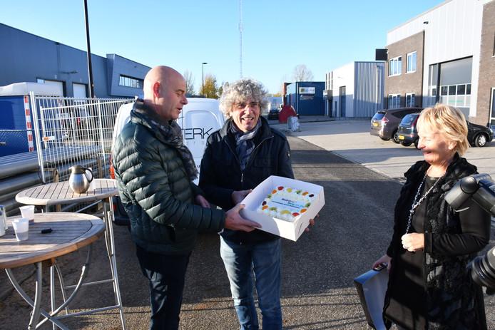 Frank Verweij (links) en Jaap Sterk met de taart: wethouder Irma van de Scheur kijkt toe.