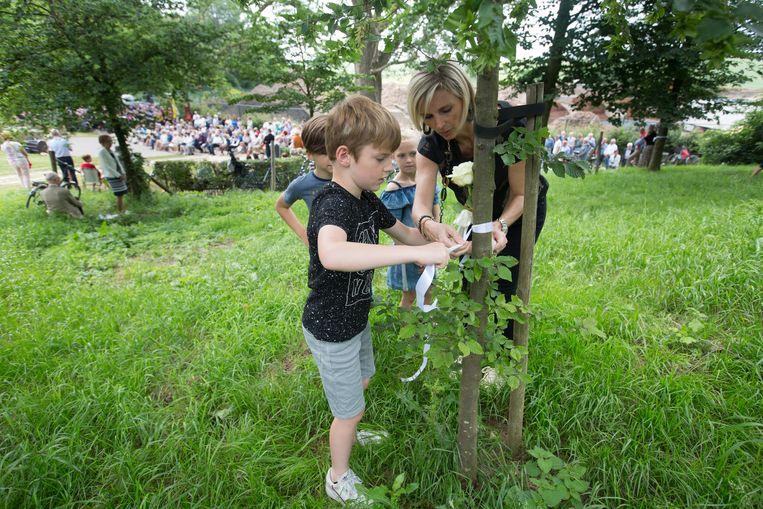 Kinderen brengen een witte roos met lint aan in achttien bomen die in het erepark aan het monument voor de slachtoffers van de Roosburgramp werden geplant.