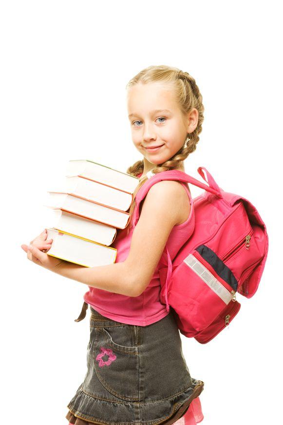 Een meisje draagt een aantal zware schoolboeken.