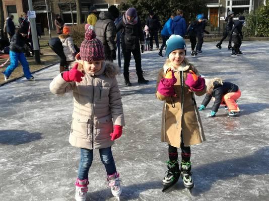 Anouk Augenbroe en Teuntje Salters (beiden 7) hebben het naar hun zin op de ijsbaan.