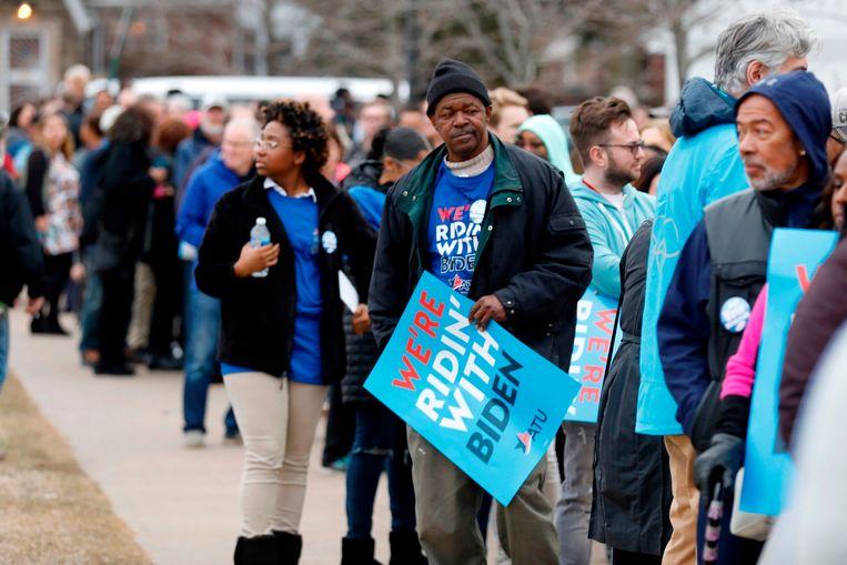 Aanhangers van Joe Biden staan in de rij om de voormalige vicepresident te horen spreken tijdens een bijeenkomst op de Renaissance High School in Detroit, Michigan. Beeld AFP
