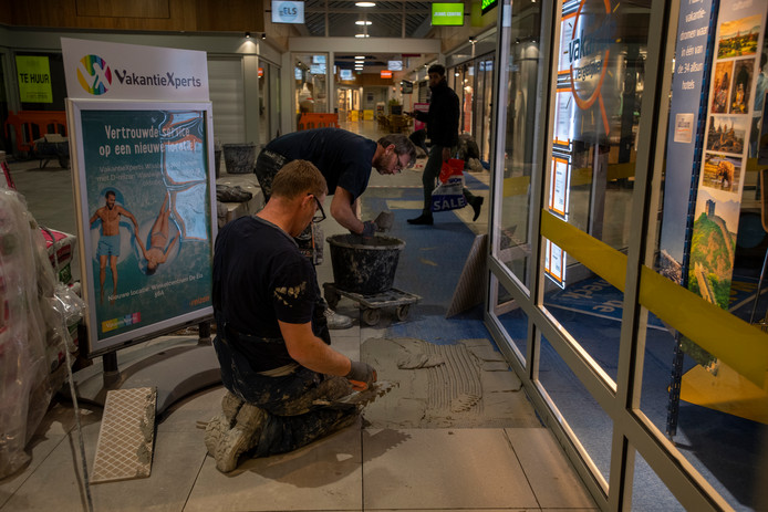 Tegelzetters werken 's avonds en 's nachts zodat klanten en winkeliers geen hinder ondervinden.
