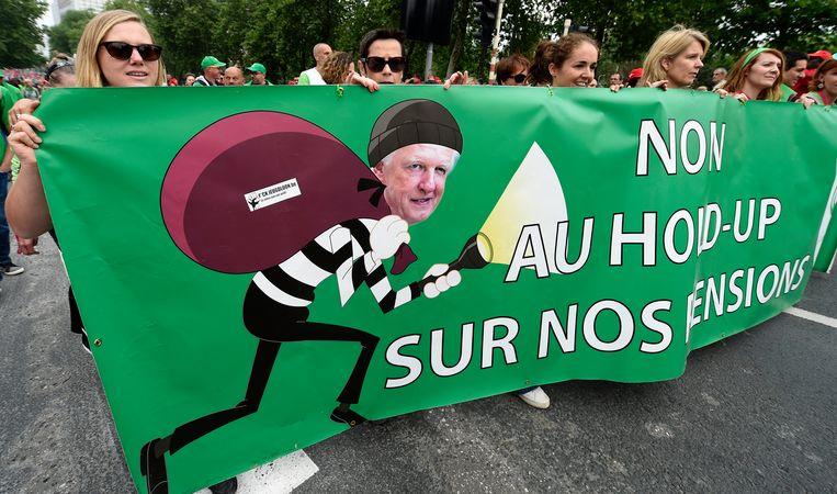 Beeld van de pensioenbetoging in Brussel gisteren. Minister van Pensioenen Daniel Bacquelaine (MR) afgebeeld als een dief die de mensen hun pensioen komt stelen.